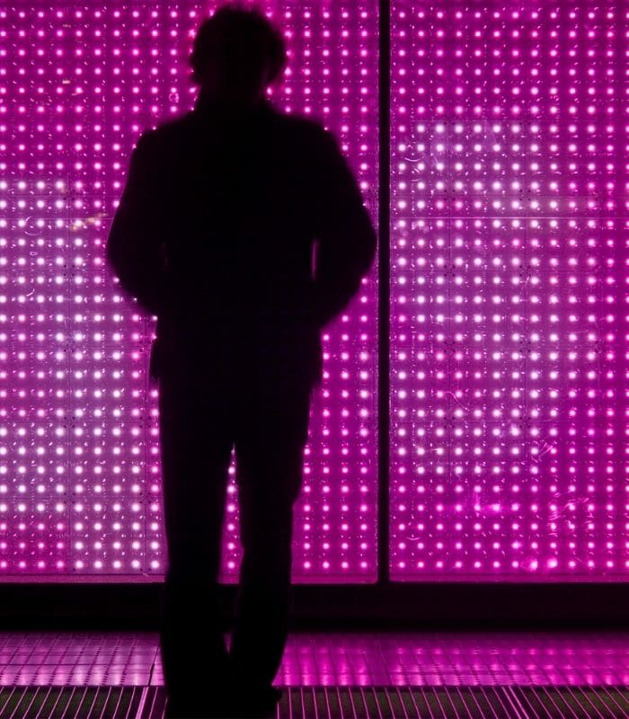 a man in front of a giant led wall
